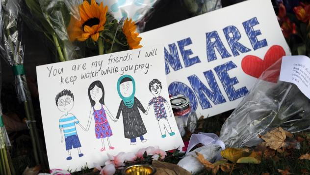 A message card is placed at a collection of flowers left at the Botanical Gardens in Christchurch, New Zealand, on Saturday. A 28-year-old white supremacist stood silently before a judge, accused in mass shootings at two mosques that left dozens of peopl