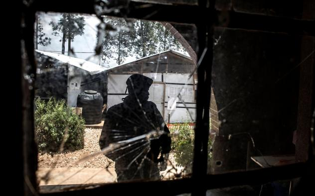 A police officer stands guard by a window riddled with bullet holes in an Ebola treatment center in Butembo, a city in Democratic Republic of the Congo. The center has been attacked twice in the last month.