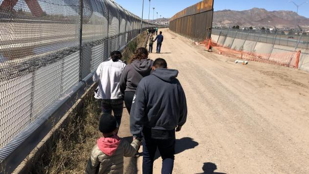 Migrants trudge along the border fence to a waiting bus after turning themselves into Border Patrol at the U.S.-Mexico border near El Paso, Texas.