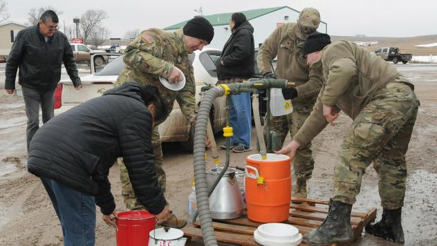 National Guard members distribute drinkable water to residents of Sharps Corner, a community in the Pine Ridge Reservation in S.D.