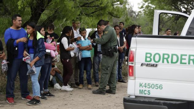A Border Patrol agent checks the names and documents of families who crossed the nearby U.S.-Mexico border near McAllen, Texas. Immigration authorities say they expect the continuing surge of Central American families crossing the border to multiply in t