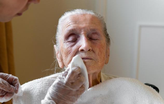 A certified nursing assistant wipes Neva Shinkle's face with chlorhexidine, an antimicrobial wash. Shinkle is a patient at Coventry Court Health Center, a nursing home in Anaheim, Calif., that is part of a multicenter research project aimed at stopping t