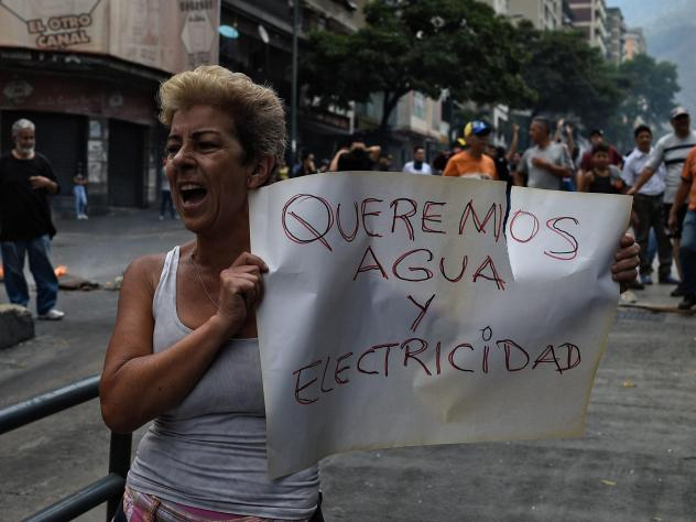 """A woman holds a placard reading """"We Want Water and Electricity"""" as she shouts slogans during a protest in Caracas, Venezuela, about a lack of water and electric service during a new power outage in the country on Sunday. President Nicolás Maduro announc"""