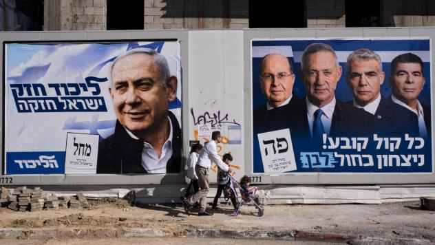 People walk by election campaign billboards showing Israeli Prime Minister and head of the Likud party Benjamin Netanyahu (left) alongside the Blue and White party leaders, including Benny Gantz. Ahead of Tuesday's election, Netanyahu has pledged to anne