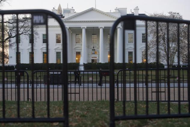 In this March 24, 2019 photo, The White House is seen behind security barriers in Washington. A White House official turned whistleblower says dozens of people in President Donald Trump's administration were granted access to classified information despi