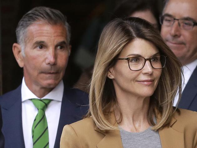 Actress Lori Loughlin and her husband, clothing designer Mossimo Giannulli (left), announced on Monday that they would plead not guilty to charges in the Justice Department's college admissions case. Here, they leave federal court in Boston earlier this