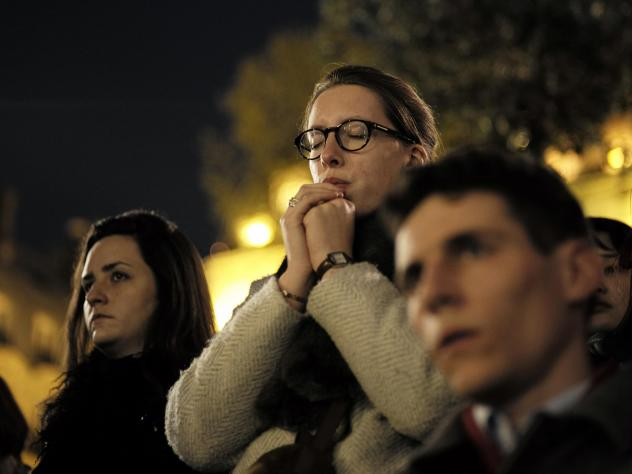 People attend a vigil in Paris on Tuesday following the devastating fire that destroyed much of the beloved Notre Dame Cathedral.