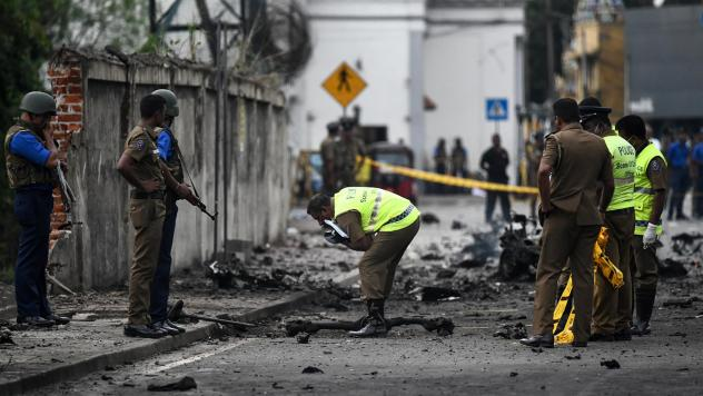 Sri Lankan security personnel inspect the debris of a van after it explodes on Monday near St. Anthony's Shrine in Colombo. More than 300 people died and more than 500 others were wounded after Sunday's attacks on churches and hotels.