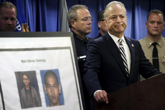 U.S. Attorney Nick Hanna stands next to photos of Mark Steven Domingo during a news conference in Los Angeles on Monday. Federal prosecutors said Domingo had planned to bomb a white supremacist rally as retribution for the New Zealand mosque attacks but