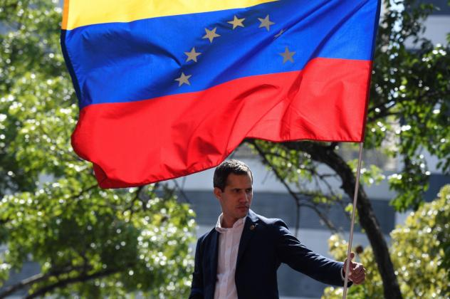 Venezuelan opposition leader and self-proclaimed acting president Juan Guaido stands under the national flag during a gathering with supporters after members of the Bolivarian National Guard joined his campaign to oust President Nicolas Maduro, in Caraca