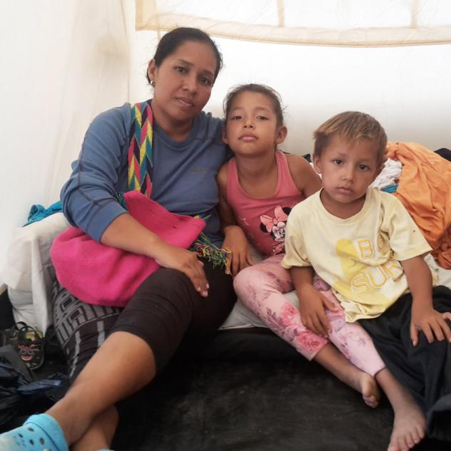 Gusmary Añez sits in a tent with two of her children. She and her husband, along with their four children, had been sleeping outdoors in Maicao, a Colombian town near the Venezuelan border. Now they live in one of 60 tents at the camp that house more th