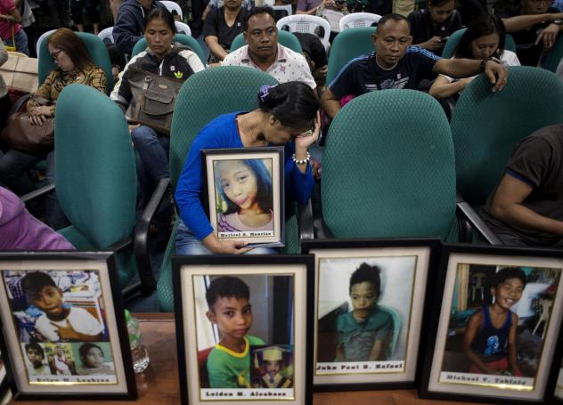 At a Feb. 21, 2018, Philippine Senate hearing in Manila on deaths linked to the dengue vaccine, families brought photos of children who had been vaccinated.