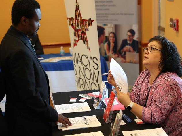 Betty Fernandez of Macy's department store speaks with a potential applicant about job openings during a job fair in Miami on April 5. Employers added far more jobs than expected in April — another sign the U.S. economy is chugging along as the expansi