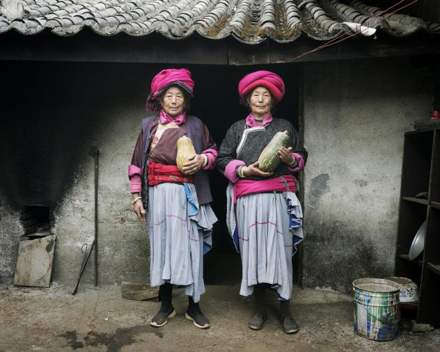 Naju Dorma, 73, and Lacuo Dorma, 66, belong to the Mosuo society in China, where grandmothers head up households. They're posing in traditional garb in their village of Luoshui.