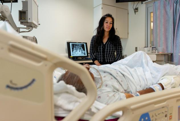 Lenh Vuong, a clinical social worker at Los Angeles County+USC Medical Center, checks on a former John Doe patient she recently helped identify.
