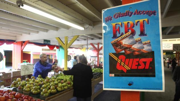A sign announces the acceptance of electronic benefit transfer cards at a farmers market in California. Anti-poverty groups fear that many low-income people might be pushed off programs such as food stamps under a possible change to how the government me
