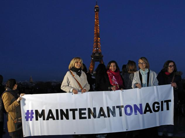 """French Culture Minister Françoise Nyssen (second right), Paris Mayor Anne Hidalgo (center) and women's rights activists hold a banner reading """"<em>Maintenant on agit</em>"""" (""""Now we act""""), on the eve of International Women's Day on March 7. They aim to r"""