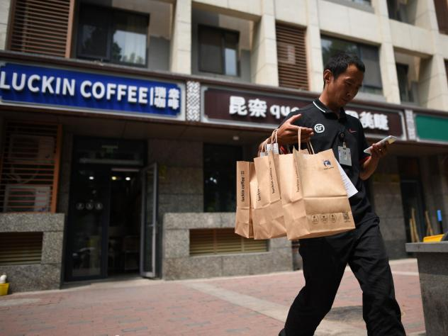 Luckin Coffee customers use an app and can pick up their coffee in three minutes or have it delivered. Above, a deliveryman in Beijing.