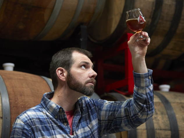 "Beer archaeologist Travis Rupp inspects his latest ""Ale of Antiquity,"" George Washington Porter, surrounded by the oak barrels it fermented in at Avery Brewing Co. in Boulder, Colo."