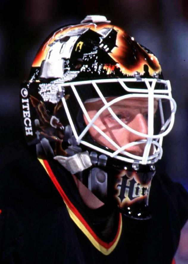 Corey Hirsch, seen during his playing days with the Vancouver Canucks. The mask, which was designed by Frank Cipra and inspired by <em>Psycho</em>, even features Alfred Hitchcock's famous silhouette above Hirsch's eyes. These days, the mask holds special