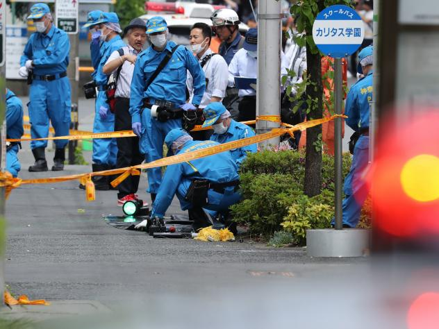 Police forensic experts investigate a crime scene where a man stabbed 19 people, including children in Kawasaki on May 28. Two people, including a child, are reportedly dead.