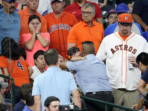 A young child is carried from the stands after being injured by a foul ball off the bat of Chicago Cubs outfielder Albert Almora Jr. during the fourth inning of a baseball game against the Houston Astros Wednesday.