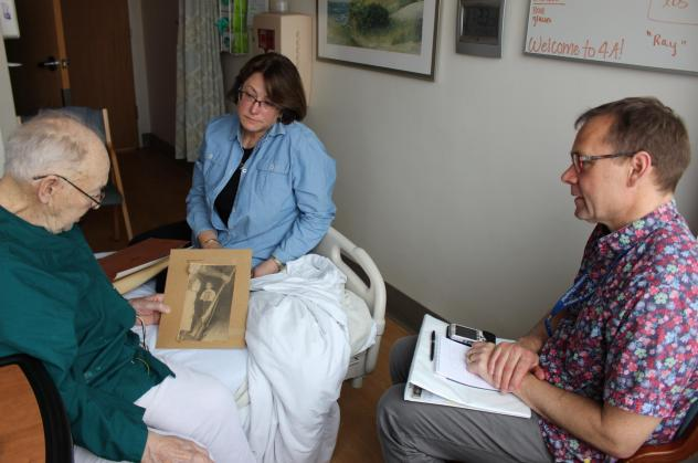 Thor Ringler (right) interviewed Ray Miller (left) in Miller's hospital room at the William S. Middleton Memorial Veterans Hospital in Madison, Wis., in April. Miller's daughter Barbara (center) brought in photos and a press clipping from Miller's time i