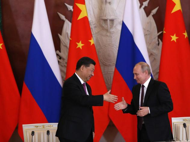 Chinese President Xi Jinping and Russian President Vladimir Putin shake hands during their meeting at the Grand Kremlin Palace on Wednesday in Moscow.