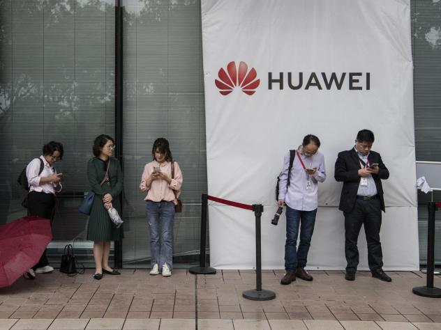 Huawei employees wait for a shuttle bus at the company's campus on April 12 in Shenzhen, China. A senior Huawei official says Google is talking with the U.S. government on behalf of the Chinese telecom giant.