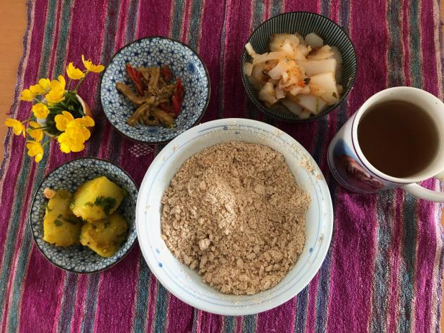 A bowl of tsampa flour pictured with other dishes in a typical Tibetan lunch. Counterclockwise from left: potatoes in turmeric and cumin; <em>liangfen;</em> mung bean jelly and spring onions with cilantro, triple-fried in red chili pepper; and black tea.