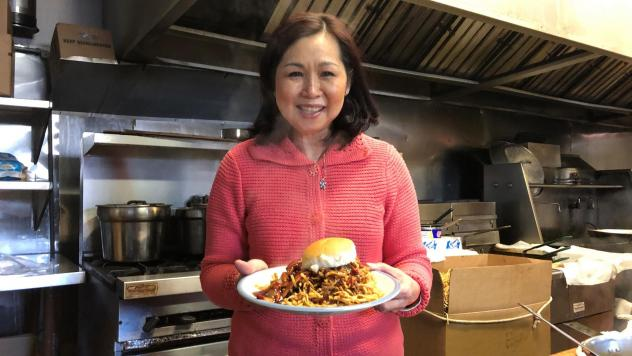 Regina Mark, co-owner of Mee Sum Restaurant in Fall River, Mass., holds a chow mein sandwich, which the restaurant has served for more than 50 years.