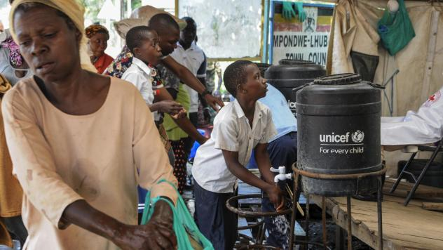 The WHO says the current Ebola outbreak is an emergency in the Democratic Republic of the Congo and the region — but not on the international level. Here, people arriving from the DRC on Friday wash their hands with chlorinated water to prevent the spr
