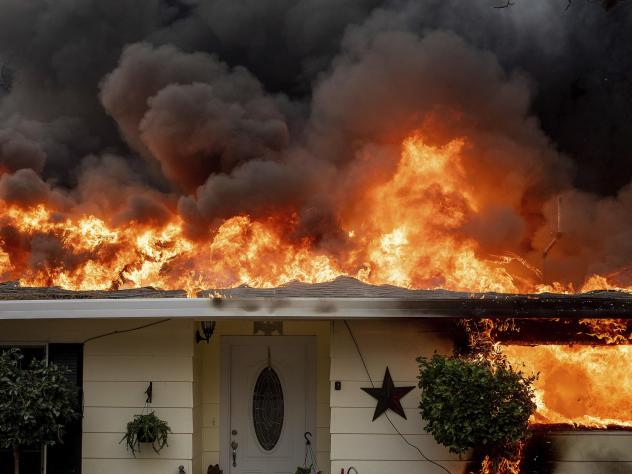 Flames consume a home in Paradise, Calif.  PG&E will pay the town and other jurisdictions $1 billion for wildfire damages caused by its equipment.
