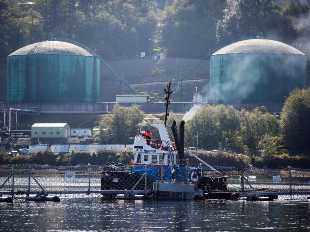 A tugboat operator secures a floating razor wire security fence during an emergency response exercise at the Kinder Morgan Inc. Westridge Marine Terminal in Burnaby, British Columbia, Canada, last September. A new expansion of the Trans Mountain pipeline