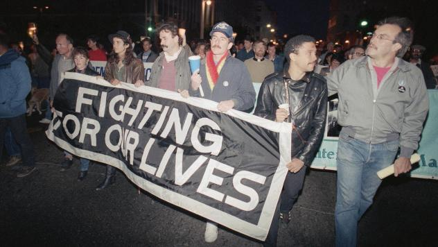 Marchers at a candlelight vigil in San Francisco, Calif., carry a banner to call attention to the continuing battle against AIDS on May 29, 1989. The city was home to the nation's first AIDS special care unit. The unit, which opened in 1983, is the subje