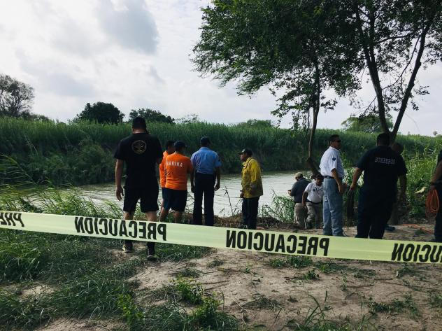 Authorities stand behind yellow warning tape along the Rio Grande bank where the bodies of Salvadoran migrant Óscar Alberto Martínez Ramírez and his 23-month-old daughter, Valeria, were found, in Matamoros, Mexico on Monday, after they drowned trying