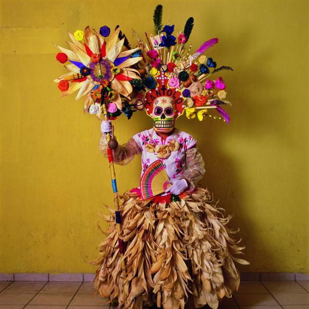 This costume, with corn husks and feathers and paper flowers, is worn by a member of a dance group that gathers in cemeteries and other places to mark Day of the Dead festivities (called Xantolo, the word written above the mask). The idea of combining a