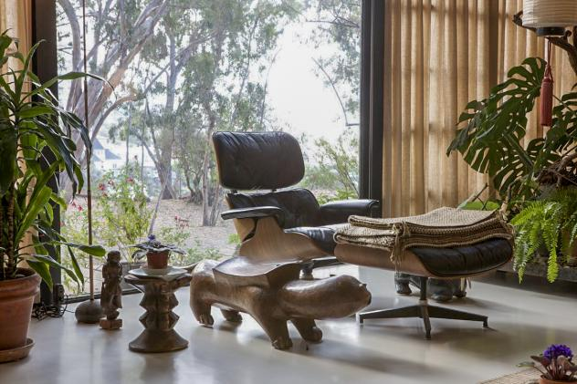 An Eames lounge chair and ottoman sit in the living room.