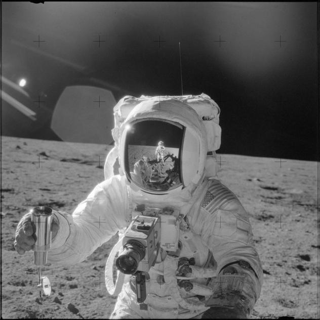 Astronaut Alan L. Bean holds a container filled with lunar soil collected during the extravehicular activity in which astronauts Charles Conrad Jr., commander, and Bean, lunar module pilot, participated.