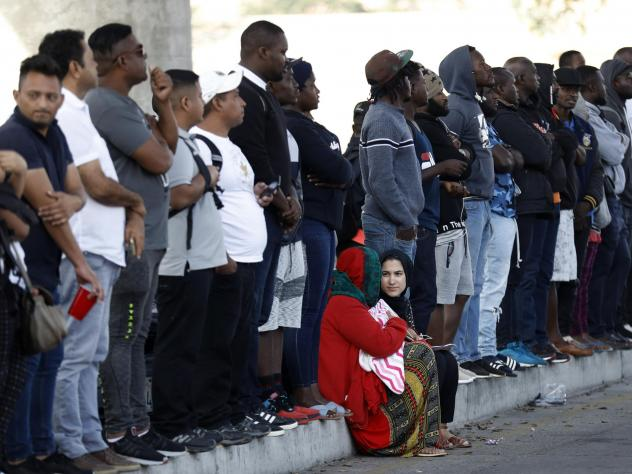 People wait in Tijuana, Mexico, on Tuesday to apply for asylum in the United States. A memo notified officers that immigrants at the southern border are ineligible for asylum, with a few exceptions.