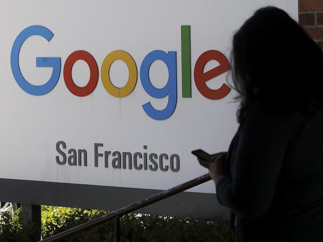 A woman walks past a Google sign in San Francisco. The Justice Department is launching an antitrust review of major online companies. The DOJ did not name the firms, but there have been increasing calls to regulate companies like Google, Facebook and Ama