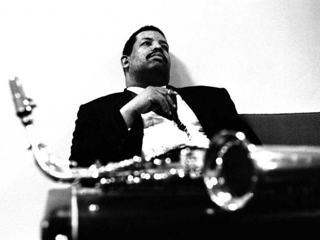 Cannonball Adderley sits with his saxophone.
