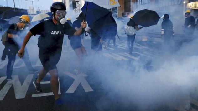 Protesters fend off tear gas and riot police in Hong Kong on Sunday. Pro-democracy demonstrations in the semi-autonomous Chinese territory have been going on for several weeks.