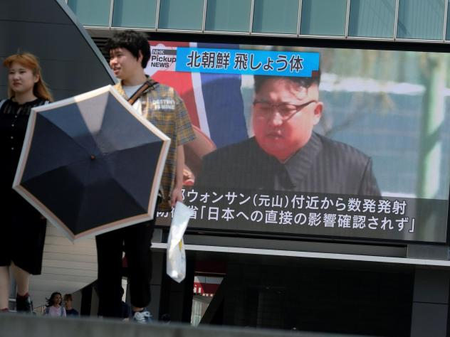 Pedestrians walk past a screen in Tokyo reporting about North Korea's test firing of a rocket system off the coast of North Korea on Wednesday.