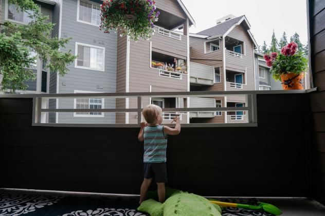 Grigory Vodolazov's 3-year-old son peers into his family's apartment complex from their unit in Bellevue, Wash. The Vodolazov family is part of Creating Moves to Opportunity, a housing voucher experiment that uses incentives and counseling to encourage l