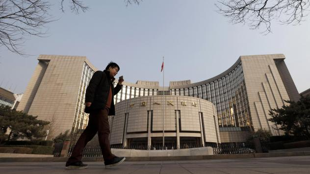 A man walks past China's central bank, or the People's Bank of China, in Beijing.