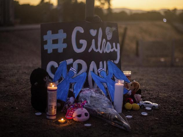 Candles burn at a makeshift memorial for Gilroy Garlic Festival shooting victims outside the festival grounds in Gilroy, Calif. The FBI says it has opened a domestic terrorism investigation into the incident.