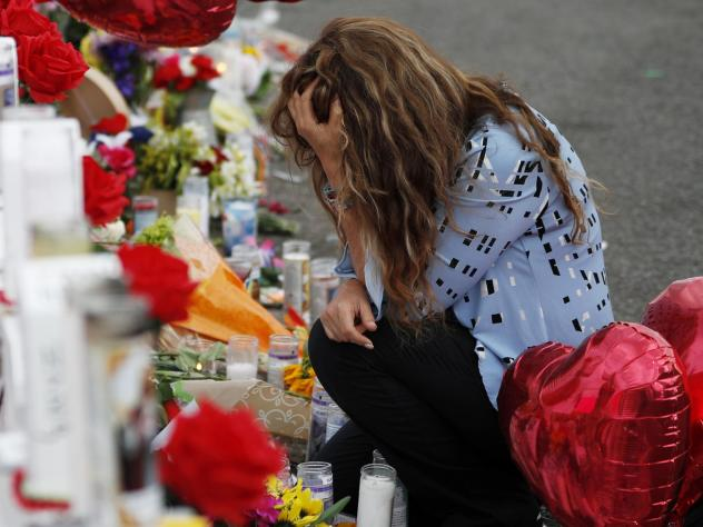 Gloria Garces kneels in front of crosses at a makeshift memorial near the scene of a mass shooting at a shopping complex Tuesday in El Paso, Texas.