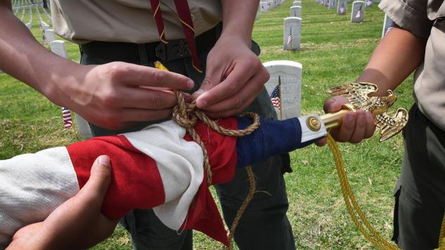 Boy Scouts at Los Angeles National Cemetery prepare a U.S. flag beside the graves of war veterans on May 25, during the annual flag placement ceremony for Memorial Day to honor the fallen.