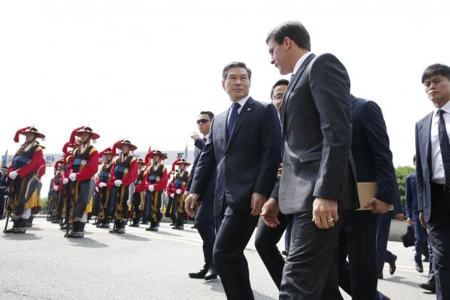 U.S. Defense Secretary Mark Esper (front right), flanked by South Korean Defense Minister Jeong Kyeong-doo (center), arrives at the Defense Ministry in Seoul, South Korea, on Friday.